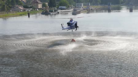 The fire brigade rescue helicopter flying in to fill with water from a river.