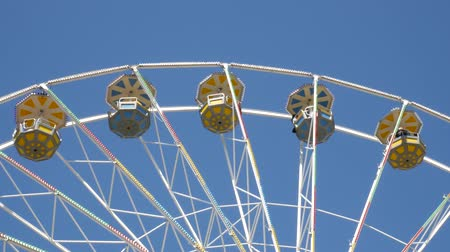 Big ferris wheel in the amusement park. Blue sky in the background. Vídeos