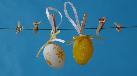 The easter egg is hanging on the clothesline on a blue background. Free space to add text. Vídeos