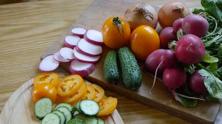 Different sliced ??vegetables, cucumber, radish, tomatoes and onions. Preparing the food in the kitchen for cooking.