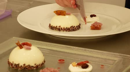 The chef decorates a plate with a sweet dessert