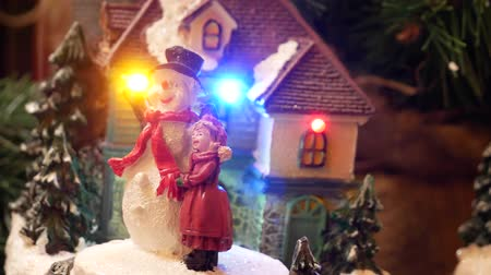 Miniature christmas decorations with a dancing doll and snowman.