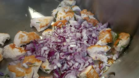 Cooking in a professional broiler. Roasted chicken pieces with onions.