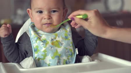 milestone : Mom give spoon baby child infant in high chair kitchen weaning solids independent toddler