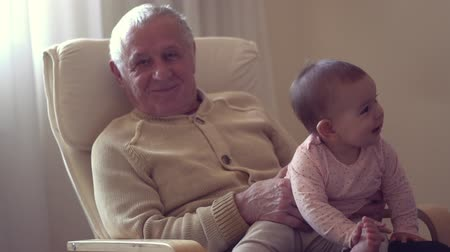 внучка : happy grandfather holds a baby on hands indoors generation happiness concept slow motion