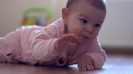 pelenka : Baby crawls toward the camera smiling and laughing in a room indoors learning activities crawling Stock mozgókép