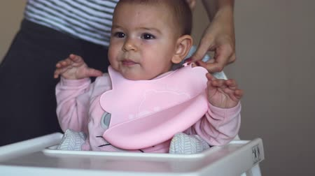 crying baby : cute baby girl in high chair in silicone bib for food concept kitchen