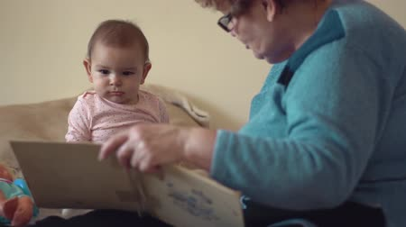 Grandmother and baby girl read a book indoors sitter grand granny family Wideo