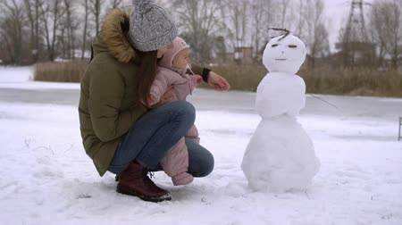 Little cute smiling babysitting outdoors in the snow snowman mother bonding time slow motion 120