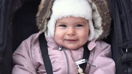 Little baby girl smiling sitting in sledge stroller on winter snow day winter outfit 4k