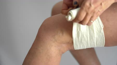 woman using elastic bandage on varicose veins legs health medicine problem to support