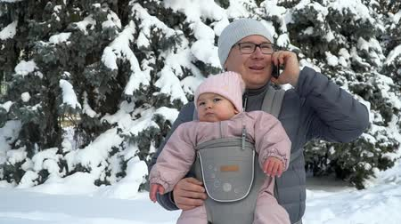 Young father with his baby in carrier with phone talking working father