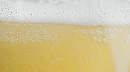 Glass of beer close-up with froth in slow motion brewery