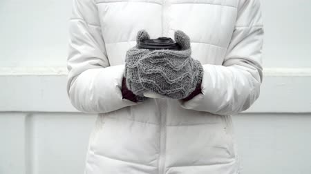 go away : Woman warming up hands in grey woolen gloves and cup of coffee or tea in winter on white background take away