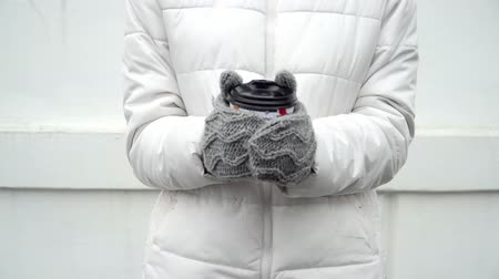 Woman warming up hands in grey woolen gloves and cup of coffee or tea in winter on white background take away