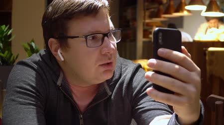 Man Make Online Video Call Using phone and wireless earphones in restaurant
