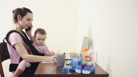 Busy Mother With Baby In Sling Carrier at home office working on laptop talking phone feeding multitasking