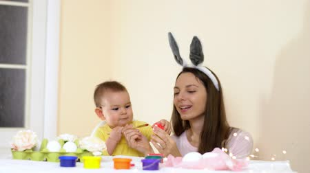 Happy Easter family mother and baby painting eggs at home seasonal traditions with bunny ears