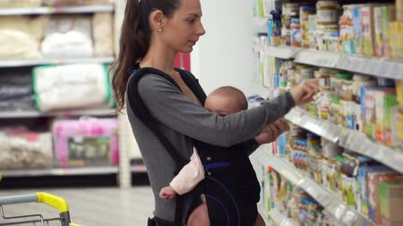 supermarket food : A young mother carrying her little baby in a sling carrier at a supermarket store buying baby food parenting concept