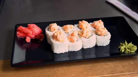 васаби : Asian food sushi in restaurant on black plate slider view slow motion