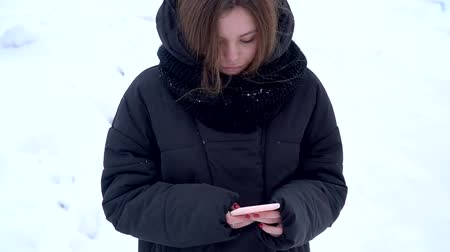Pretty caucasuian girl teenager using phone outside in winter without grloves social media concept blogger slow motion