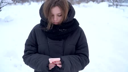 escrever : Pretty caucasuian girl teenager using phone outside in winter without grloves social media concept blogger slow motion