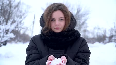 Young woman enjoying winter day outdoors Slow motion throwing snow from hands and smiling teenager Wideo
