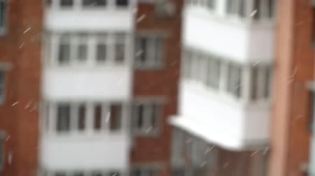4k video of falling snow outdoors on building background urban season christmas