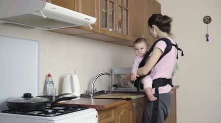 приложение : Busy Mother With Baby In Sling At Home washing dirty dishes 4k Стоковые видеозаписи