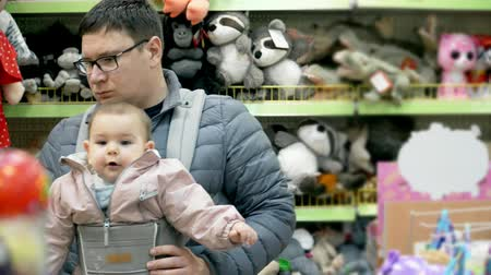 bakkal : Ukraine, Poltava - January 05 2019 Father with his child in baby carrier in the shopping mall, attachment parenting