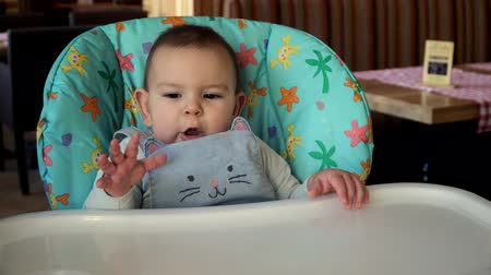 faminto : Cute caucasian baby girlsitting and yawning on a high chair in cafe 4k