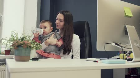 infant formula : Working mother with toddler at baby friendly office, working sucsessful female entrepreneur modern motherhood Stock Footage