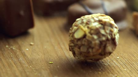 konfekció : Hand made chocolate candies falling on wooden background, tasty sweets in slow motion uhd