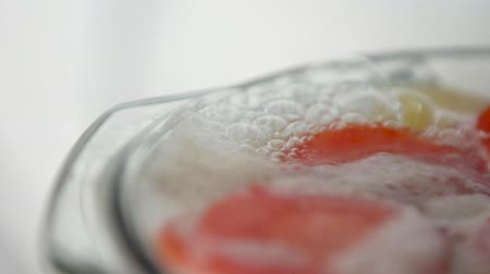 caldo : Slow motion of boiling soup broth with carrot and potato in glass pan