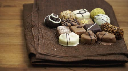 konfekció : Hand made chocolate candies falling on wooden background, tasty sweets in slow motion Stock mozgókép
