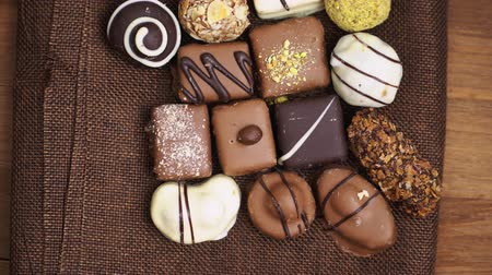 íz : Hand made chocolate candies falling on wooden background, tasty sweets in slow motion Stock mozgókép