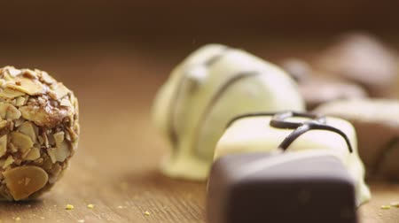 yermantarı : Hand made chocolate candies falling on wooden background, tasty sweets in slow motion uhd
