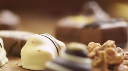 desire : Hand made chocolate candies falling on wooden background, tasty sweets in slow motion uhd
