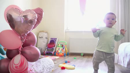 curiosidade : Little baby girl with ballons at home walking first steps on her birthday, one year