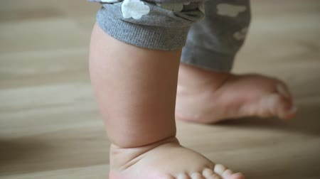 learning to walk : close-up of childrens legs taking their first steps and falling down Stock Footage