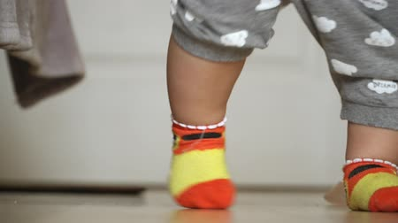 happy socks : close-up of childrens legs taking their first steps and falling down Stock Footage