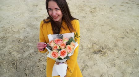 populus : Girl happily dancing with bouquet of roses bombastic in yellow coat, close up