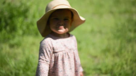 pokrývka hlavy : baby girl standing on the grass in straw hat and dress, funny belly, hot weather