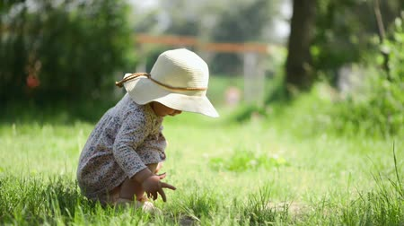 pokrývka hlavy : baby girl sittingon the grass in straw hat and dress, summer day