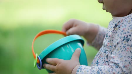ancinho : Child holds sand bucket close up on green blurred background, summer day
