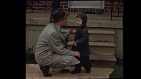 1950s Little boy gives dad hug and kiss and walks off