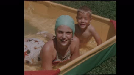 Little boy and girl play in kiddie pool 1957 Close Up `