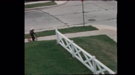 goes : 1956 Young boy with toy gun and hat plays cowboy on Tricycle Stock Footage
