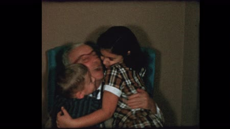 período : 1956 Grandfather gets hugs and kisses from grandchildren