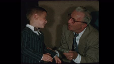 Grandfather counts out and gives grandson money 1956